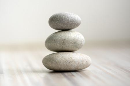 Armonía y equilibrio, mojones, piedras de equilibrio simple sobre fondo gris blanco claro de madera, escultura de rock zen, cinco guijarros blancos, torre única, simplicidad Foto de archivo