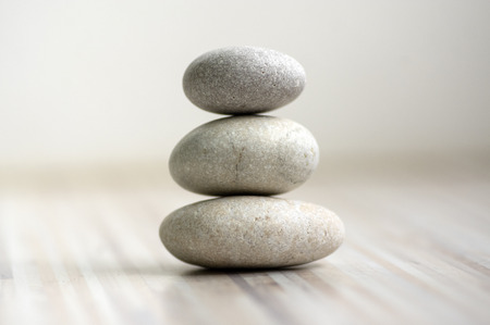 Armonia ed equilibrio, ometti, semplici pietre di equilibrio su fondo grigio bianco chiaro di legno, scultura zen di roccia, cinque ciottoli bianchi, torre singola, semplicità Archivio Fotografico