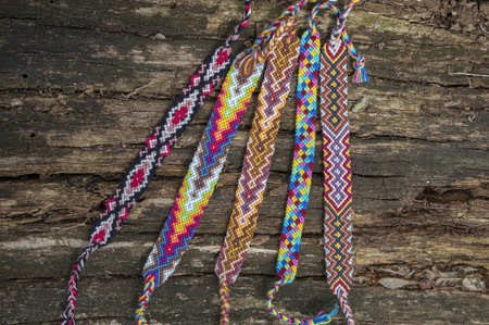 Group of colorful handmade homemade natural woven bracelets of friendship on old wood background, rainbow colors, checkered pattern, bright colors