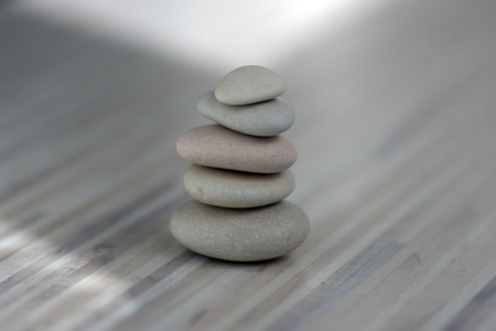 Harmonie und Balance, Steinhaufen, einfache Poise-Kiesel auf hellweißem Holzhintergrund, Einfachheit Rock-Zen-Skulptur, Flusssteine in Türmen