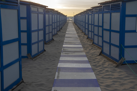 Blue white shelters on sandy beach in italian Sottomarina, public shore early morning in sunrise, nobody, calm place