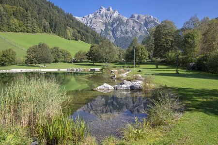 Public biotope swimming pool lake in Verfenweng surrounded by Alps, beautiful rocks in water level reflection, amazing greenery place with beautiful alpine meadow, blue sky