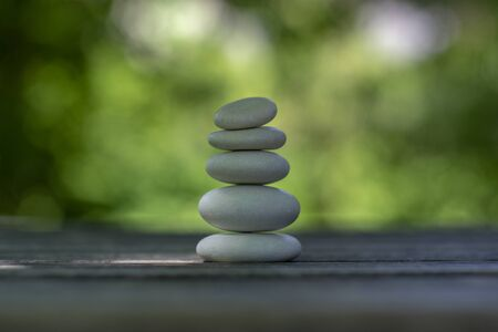 Harmony and balance, cairns, simple poise pebbles on wooden table, natural green background, simplicity rock zen relaxation sculpture