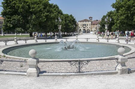 Padua  ITALY - June 12, 2017: Beautiful summer day on Prato della Valle square with water canal. Amazing white italian sculptures. Greenery, blue sky and sunlight.