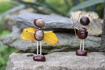 Angel and devil figures made from chestnuts and safety matches and dry leaves in the autumn garden