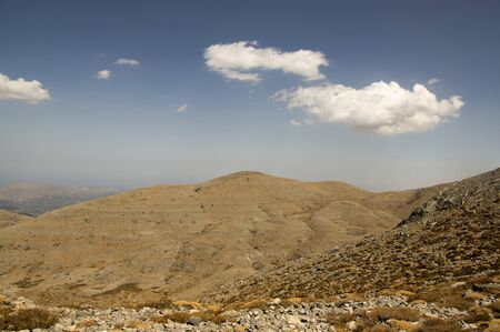 Greek Crete mountain range with highest mountain Ida Psiloritis, very dry hard terrain with sharp rocks and stones, natura park, blue sky with white clouds