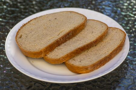 Slices of simple common wheat bread on white plate, ready to eat, food and drink 写真素材
