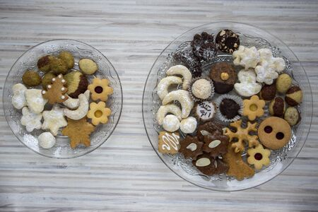 Many kinds of Christmas cookies on cut glass transparent plates, sweet food on wooden table, two dishes