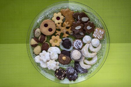Many kinds of Christmas cookies on cut glass transparent plates, green place setting on the table, flat lay image