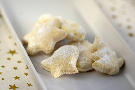whipped cream delicious cookies with sugar icing on white ceramic plate, tablecloth with golden stars, group of shapes, stars trees and bells