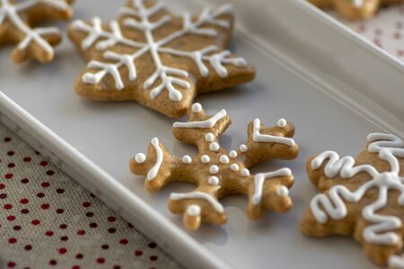 Painted traditional Christmas gingerbreads snowflakes and stars arranged on white dish in daylight, dotted tablecloth, common czech tasty sweets 写真素材