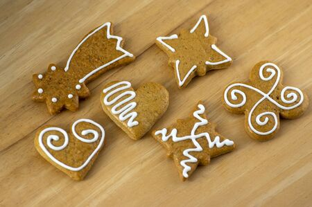 Painted traditional Christmas gingerbreads arranged on wooden background in daylight, common tasty sweets