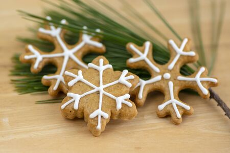 Painted traditional Christmas gingerbreads arranged on wooden background in daylight, common tasty sweets on green pine branch needles, snowflakes and stars