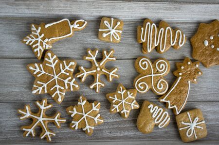 Painted traditional Christmas gingerbreads snowflakes and stars arranged on wood table in daylight, common czech tasty sweets 写真素材