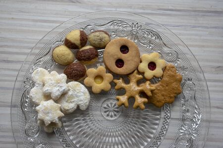 Many kinds of Christmas cookies on cut glass transparent plate, sweet food on wooden table, partially occupied 写真素材