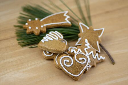 Painted traditional Christmas gingerbreads arranged on wooden background in daylight, common tasty sweets on green pine branch needles