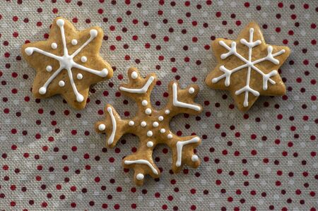 Painted traditional Christmas snowflakes gingerbreads arranged on dotted tablecloth, common czech tasty sweets, group of sweets 写真素材
