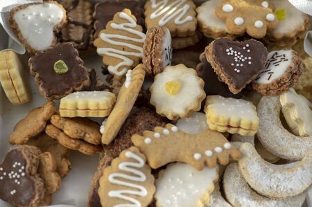 Many kinds of Christmas cookies in one pile in the box, various colors and tastes with decorations or sugar icing