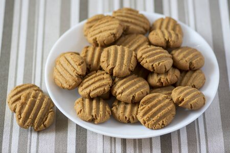 Pile of peanut butter biscuits on white plate, very tasty golden baked sweets, cookies served ready to eat