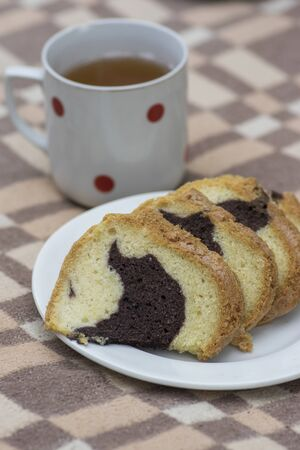 Gugelhupf on white plate on picnic blanket, very tasty edible two-colored Czech sweet cake called babovka, ready to eat, sliced sweet biscuit