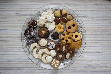Many kinds of Christmas cookies on cut glass transparent plate, sweet food on wooden table, full dish