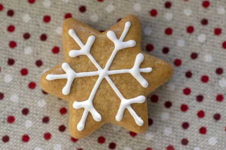 Painted traditional Christmas star gingerbread arranged on dotted tablecloth, common czech tasty sweets, one piece 写真素材