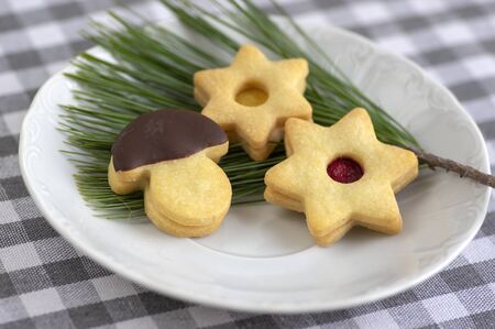 Christmas linzer sweets and cookies made from shortcrust pastry, various shapes filled with marmalade, decorated with chocolate, mushrooms and stars