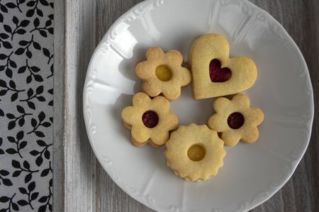 Christmas linzer sweets and cookies made from shortcrust pastry, various shapes filled with marmalade, decorated with chocolate, mushrooms, stars and hearts on white plate 写真素材