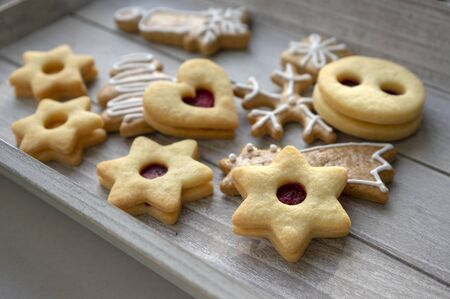 Christmas linzer sweets and gingerbread sweets, various shapes on gray wooden tray, ready to eat