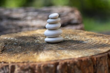 White five stones cairn in daylight, poise light pebbles on wooden stump in front of green natural background, zen like sculpture, simplicity, harmony and balance Stock fotó