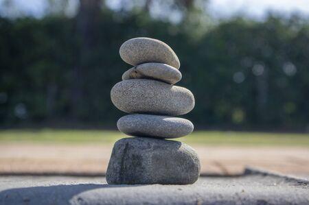 Five stones cairn tower, rock zen sculpture, brown beige pebbles in sunlight