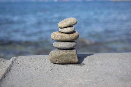 Five stones cairn tower, rock zen sculpture, brown beige pebbles and sea light blue background in sunlight
