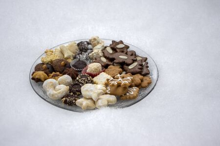 Many kinds of Christmas cookies on two cut glass transparent plates outdoors in white snow