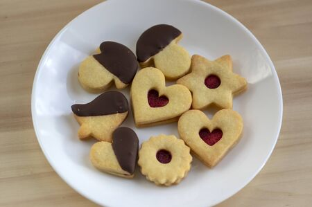 Christmas linzer sweets and cookies made from shortcrust pastry, various shapes filled with marmalade, decorated with chocolate, mushrooms, stars and hearts on white plate Stock fotó
