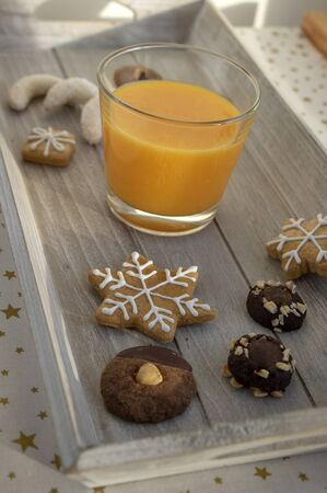 Group various kinds of delicious sweet Christmas cookies on light gray wood, fresh orange juice, close up view of tasty holiday breakfast in daylight