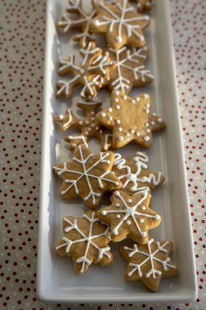 Painted traditional Christmas gingerbreads snowflakes and stars arranged on white dish in daylight, dotted tablecloth, common czech tasty sweets Stock fotó