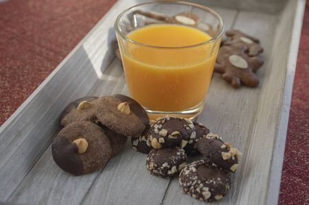 Group various kinds of delicious sweet Christmas cookies on light gray wood with fresh orange juice, moravian gingerbread, chocolate biscuits covered with nuts, sweets with hazelnut