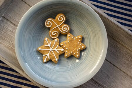 Various shapes of Christmas gingerbread cookies on light blue bowl on wooden table, group of star shapes Stock fotó - 140563065