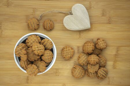 Very tasty peanut butter biscuits on bamboo wooden board in white baking bowl and decorative wood heart, golden baked healthy cookies, delicious taste