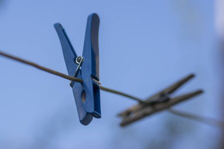 Group of plastic and wooden clothes pegs hanging on clothesline against blue sky, blue background