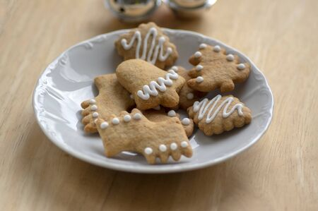 Various shapes of Christmas gingerbread cookies on white plate on wooden table, small group of simplicity winter sweets with decorative icing Stockfoto