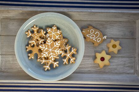 Various shapes of Christmas gingerbread cookies on light blue bowl on wooden table, group of star shapes, pig with pour feliciter 2020
