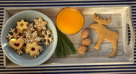 Various shapes of Christmas gingerbread cookies on light blue bowl on wooden table, group of star shapes and one reindeer, beverage orange juice