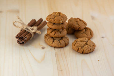 Very tasty peanut butter biscuits on bamboo light brown wooden board, golden baked healthy, raw cinnamon tied with jute twine Standard-Bild