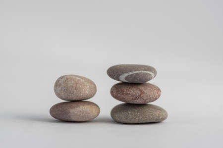 Two simplicity stones cairns isolated on white background, group of light five gray white pebbles built in two towers, harmony and balance