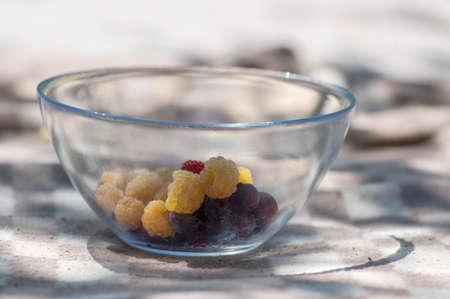 Glass bowl with summer berries, healthy breakfast on brown picnic blanket in sunlight, group of strawberries, blackberries, raspberries and serviceberries