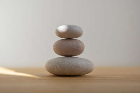 Stone cairn on striped gray white background, three stones tower, simple poise stones, simplicity harmony and balance, rock zen sculpture Standard-Bild