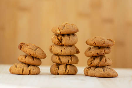 Very tasty peanut butter biscuits on bamboo light brown wooden board, golden baked healthy, built in three towers