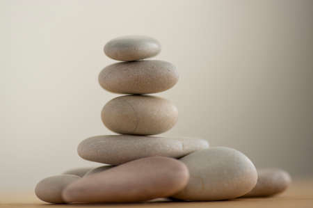 One simplicity stones cairn isolated on white background, group of light gray pebbles built in tower, wooden table, harmony and balance