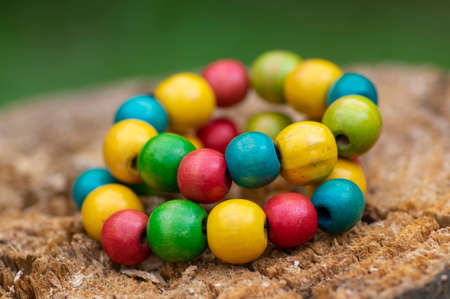 Colorfull wooden craft beads on thread, fashionable beaded bracelets, bright beautiful colors green red yellow and light blue on wood background